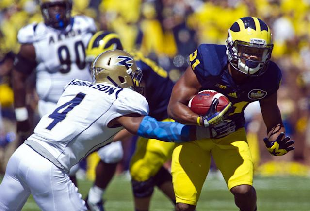 Akron safety Johnny Robinson (4) attempts to tackle Michigan wide receiver Jeremy Gallon (21) during the second quarter of an NCAA college football game, Saturday, Sept. 14, 2013, in Ann Arbor, Mich. (AP Photo/Tony Ding)
