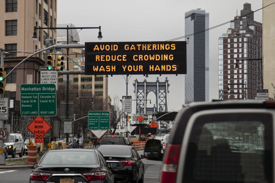 FILE - In this Thursday, March 19, 2020 file photo, The Manhattan bridge is seen in the background of a flashing sign urging commuters to avoid gatherings, reduce crowding and to wash hands in the Brooklyn borough of New York. A year after becoming a global epicenter of the coronavirus pandemic, New York and New Jersey are back atop the list of U.S. states with the highest rates of infection.(AP Photo/Wong Maye-E, File)