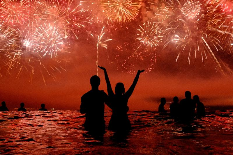 People watch fireworks during New Year celebrations at Copacabana beach in Rio de Janeiro (AFP Photo/Yasuyoshi Chiba)