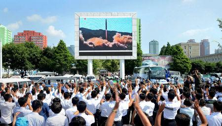 FILE PHOTO: People watch a huge screen showing the test launch of intercontinental ballistic missile Hwasong-14 in this undated photo released by North Korea's Korean Central News Agency (KCNA), July 5, 2017. KCNA/via REUTERS/File Picture