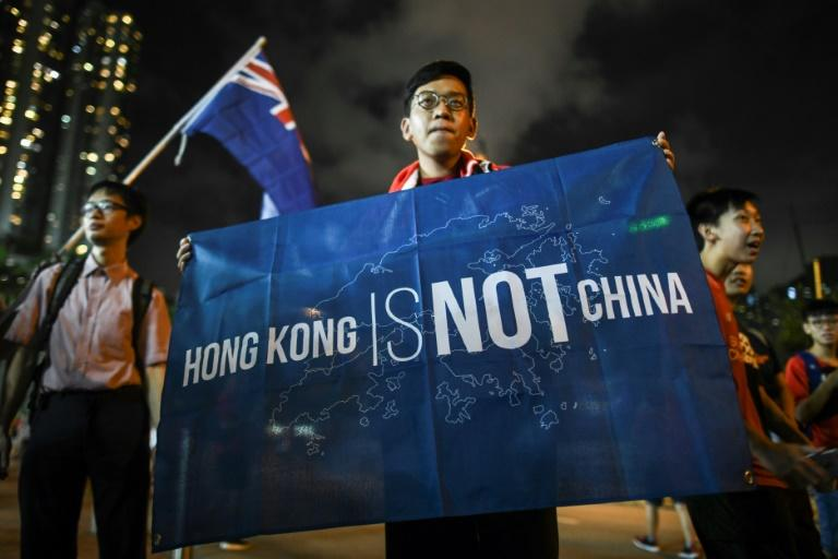 "A football fan displays a banner reading ""Hong Kong is not China"" in front of another fan carrying the old British colonial flag (back L) after a match in Hong Kong"