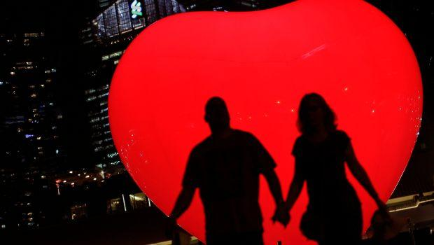 a couple is silhouetted against a heart