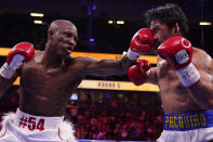 Yordenis Ugas, left, of Cuba, hits Manny Pacquiao, of the Philippines, in a welterweight championship boxing match Saturday, Aug. 21, 2021, in Las Vegas. (AP Photo/John Locher)
