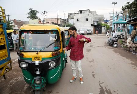 Danish Maqbool Malik pays to an auto rickshaw driver upon reaching at a railway station after meeting his brother Uzair Maqbool Malik in a central jail, in Agra