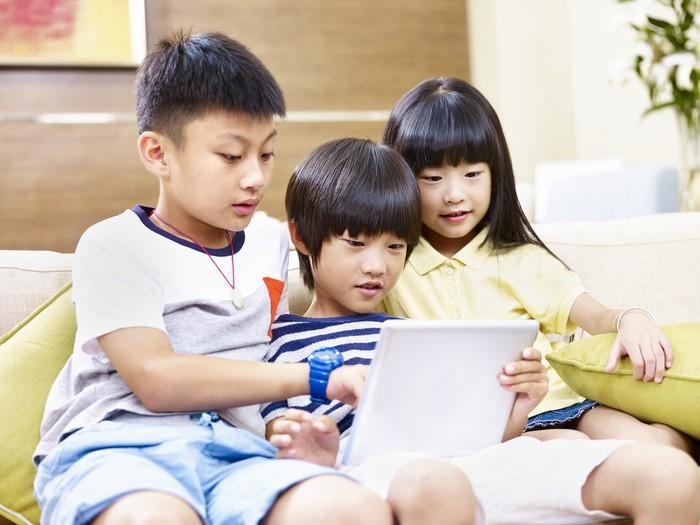 Three young children sitting on a couch looking at a tablet.