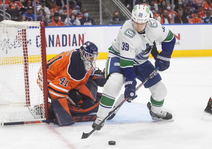 Vancouver Canucks' Alex Chiasson (39) picks up a rebound from Edmonton Oilers goalie Mike Smith (41) during the third period of an NHL hockey game Wednesday, Oct. 13, 2021, in Edmonton, Alberta. (Jason Franson/The Canadian Press via AP)