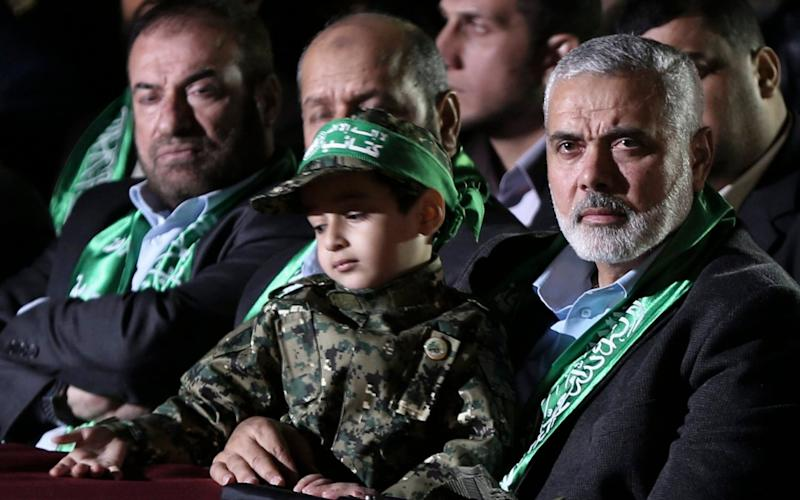 Hamas senior leader Sheikh Ismaeil Haneiya (R) seated with the son of Mazen Faqaa, senior leader of Ezz-Al Din Al Qassam Brigades, the armed wing of the Palestinian Hamas movement, at a memorial service in Gaza City - Credit:  EPA/MOHAMMED SABER