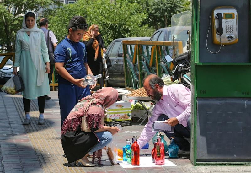 An Iranian woman checks objects sold by a street vendor in Tehran on June 15, 2019. Former Tehran mayor and prominent reformist Mohammad Ali Najafi will stand trial next month on charges of murdering his wife, the government-run Iran newspaper has said
