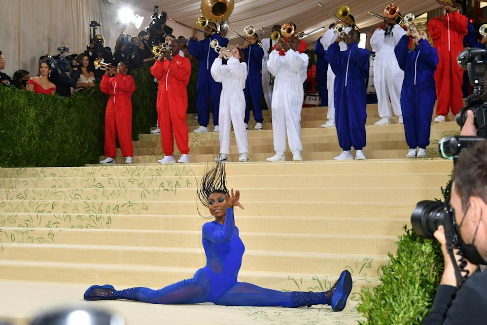 <p>opened the benefit with a bang, performing a gymnastics routine on the gala's stairs with the Brooklyn United marching band (wearing red, white and blue!) behind her.</p>