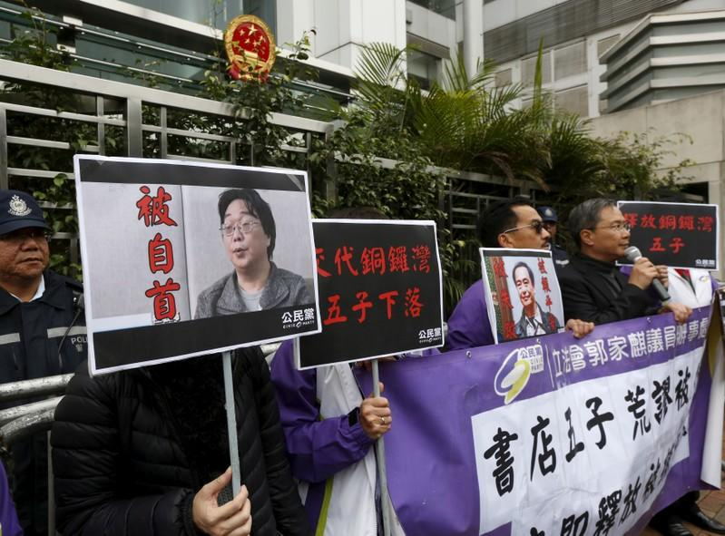 FILE PHOTO: Pro-democracy activists carry a portrait of Gui Minhai (L) during a protest outside the Chinese Liaison Office in Hong Kong