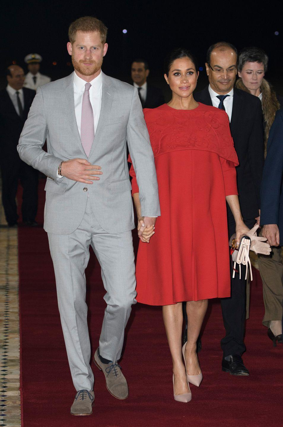 "<p>The Duchess of Sussex wore a red Valentino cape dress and nude pumps as she arrived with Prince Harry in Casablanca, Morocco to start off their royal tour. Meghan carried a pair of beige gloves and a <a href=""https://www.farfetch.com/shopping/women/valentino/items.aspx?"" rel=""nofollow noopener"" target=""_blank"" data-ylk=""slk:Valentino Garavani"" class=""link rapid-noclick-resp"">Valentino Garavani</a> clutch. </p><p><a class=""link rapid-noclick-resp"" href=""https://www.neimanmarcus.com/p/valentino-garavani-vee-ring-medium-colorblock-leather-shoulder-bag-prod218040102"" rel=""nofollow noopener"" target=""_blank"" data-ylk=""slk:Shop Similar"">Shop Similar</a> <em>Vee Ring Medium Shoulder Bag, Valentino Garavani, $3,295</em><em><br></em></p>"
