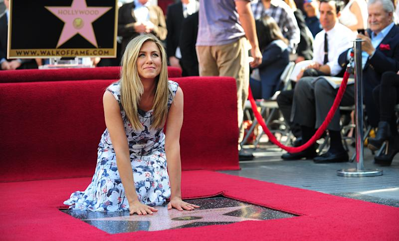 """Actress Jennifer Aniston touches her just unveiled Star on Hollywood's Walk of Fame on February 22, 2012 in Hollywood, California. Born in southern California, Aniston, perhaps best known for her role as Rachel in the classic television comedy """"Friends"""", received the 2,462nd Star on the Hollywood Walk of Fame. AFP PHOTO / Frederic J. BROWN (Photo credit should read FREDERIC J. BROWN/AFP via Getty Images)"""
