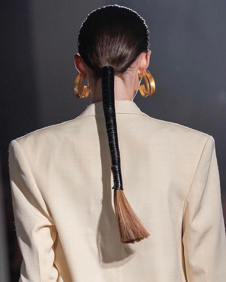 The low ponytail gets tied up this season at Proenza Schouler. The collection provides a minimalist perspective on the 80's. The hair was clean and slicked back in the front, and when the models rounded the corner, a straight, blunt, wrapped-up ponytail could be seen.