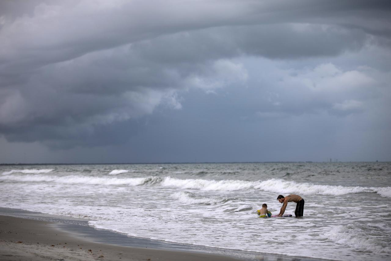 Beachgoers play in the surf near the Cocoa Beach Pier in Cocoa Beach, Florida, USA, 30 August 2019. Floridians are stocking up on supplies in preparation for Hurricane Dorian, which is expected to make landfall late on 04 September. (EPA/JIM LO SCALZO)