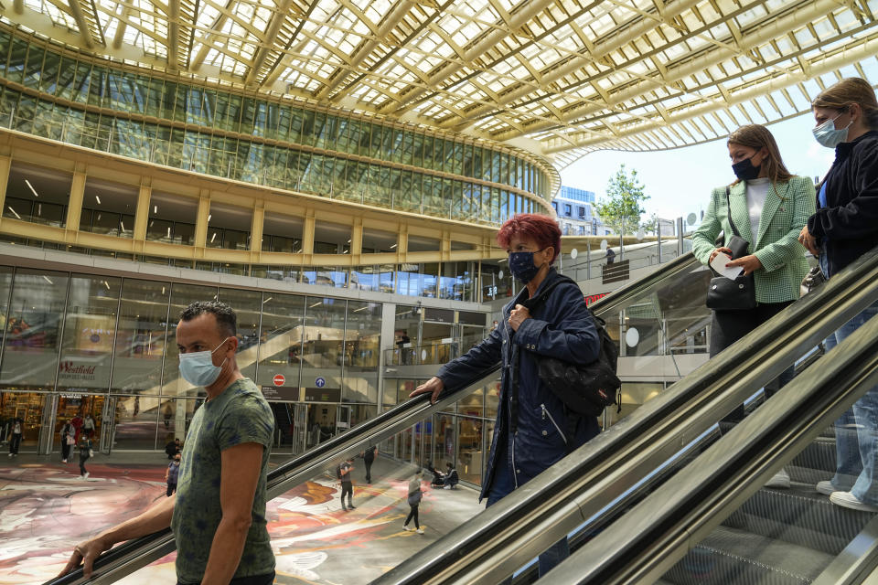 People wearing a face mask to protect against coronavirus ride an escalator at a shopping center in Paris, Friday, July 30, 2021. Vaccination rates are picking up again in France as the government requires a virus pass for more and more activities. (AP Photo/Michel Euler)