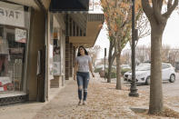 Alexandra Orozco walks down the main street of Delano, Calif., on Sunday, Dec. 6, 2020. Just over a two-hour drive from Los Angeles, the population of Delano is roughly 50,000, and jobs are scarce, she says. (Madeline Tolle/The Fuller Project via AP)
