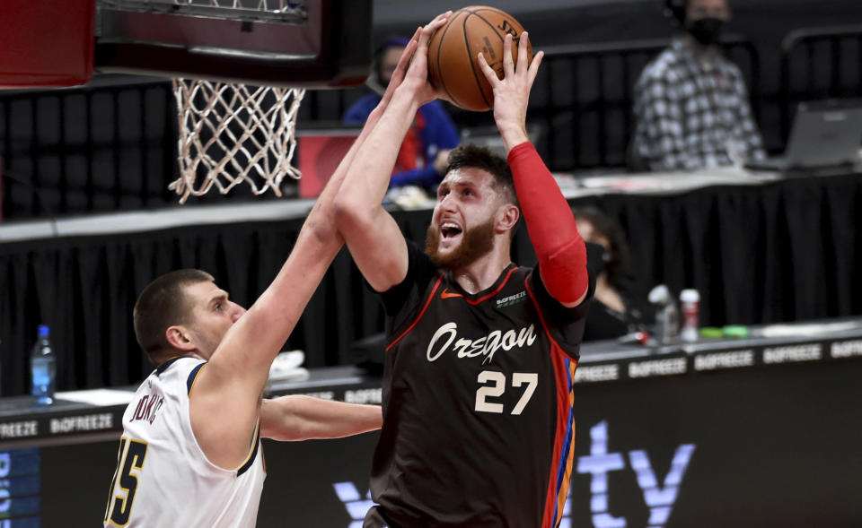 Portland Trail Blazers center Jusuf Nurkic, right, is fouled by Denver Nuggets center Nikola Jokic, left, as he drives to the basket during the first half of an NBA basketball game in Portland, Ore., Sunday, May 16, 2021. (AP Photo/Steve Dykes)