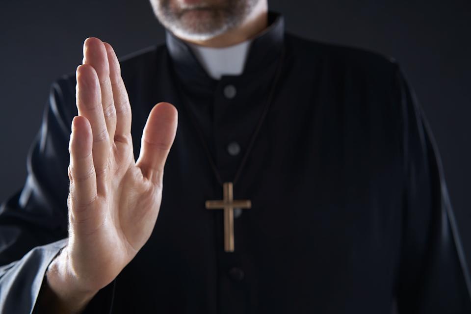 Priest hand blessing closeup with cross and clergyman background
