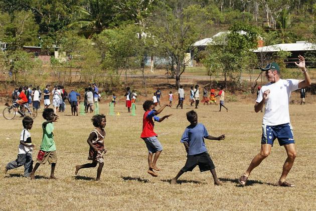 John Buchanan of Australia leads some locals through a drill on July 22, 2003 during a team visit to an Aboriginal settlement on Melville Island off the coast of Darwin, Australia. (Photo by Hamish Blair/Getty Images)