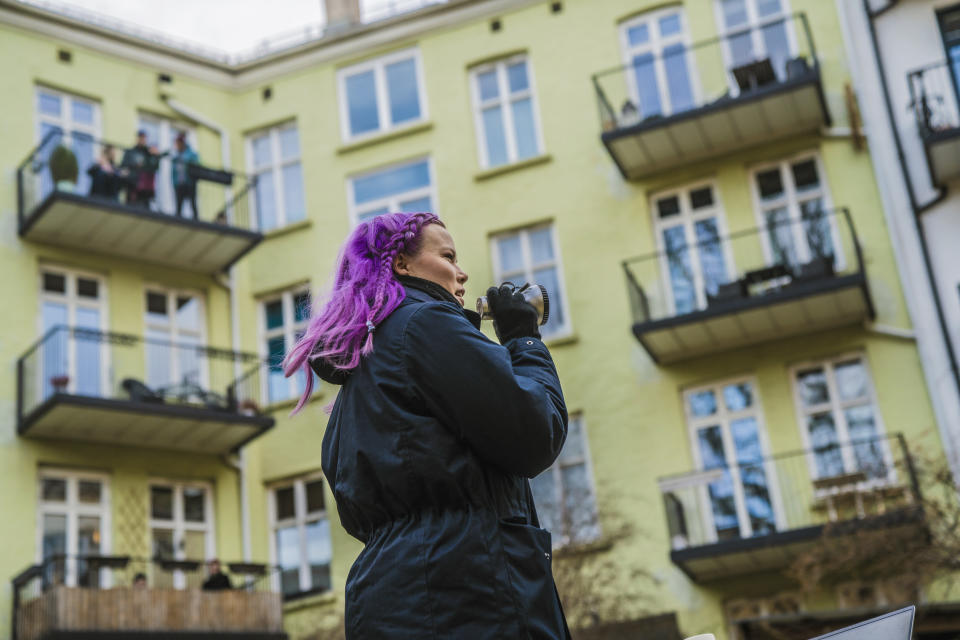 Anna Nohr speaks using a loud speaker as she invites her neighbours to take part in a backyard quiz, in Oslo, Norway, Monday, March 23, 2020, as people stay in the wake of the coronavirus. (Stian Lysberg Solum /NTB scanpix via AP)