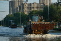 A bulldozer drives along a flooded street in Xinxiang in central China's Henan Province, Monday, July 26, 2021. Forecasters Monday said more heavy rain is expected in central China's flood-ravaged Henan province, where the death toll continues to rise after flash floods last week that killed dozens of people. (AP Photo/Dake Kang)