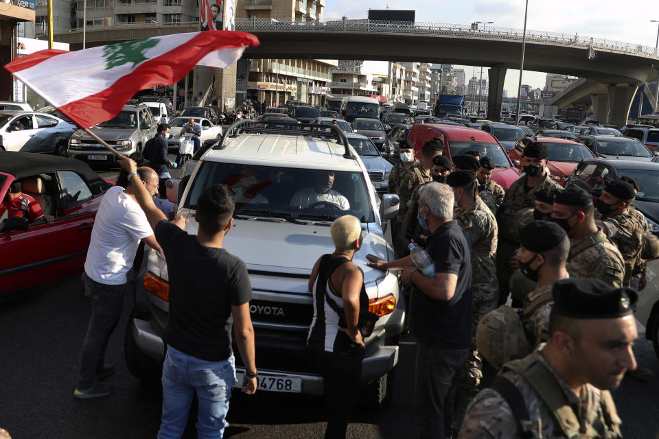 Lebanese army soldiers stand guard as protesters block a main highway, in the town of Jal el-Dib, north of Beirut, Lebanon, Thursday, June 24, 2021. Dozens of angry protesters, angered by deteriorating living conditions and government inaction, partially blocked Beirut's main highway to the capital's only airport, turning trash bin over and setting tires on fire. (AP Photo/Bilal Hussein)