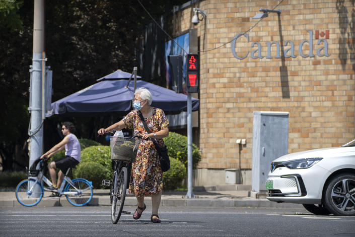 A woman walks her bicycle across an intersection near the Canadian Embassy in Beijing, Tuesday, Aug. 10, 2021. A Chinese court has rejected an appeal by a Canadian whose sentence in a drug case was increased to death after an executive of tech giant Huawei was detained in Vancouver. (AP Photo/Mark Schiefelbein)