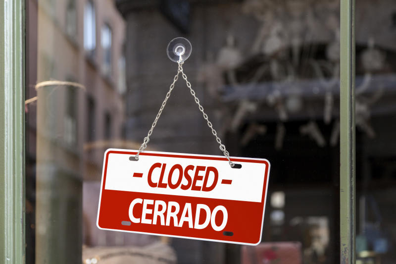 Close-up on a red Closed sign in a window with written in it in Spanish and English.