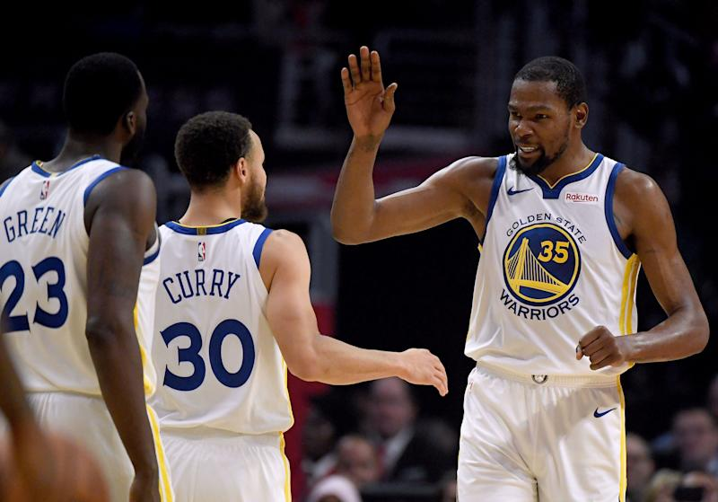 LOS ANGELES, CALIFORNIA - APRIL 26: Kevin Durant #35 of the Golden State Warriors celebrates a double digit lead lead over the LA Clippers with Stephen Curry #30 and Draymond Green #23 in the first half during Game Six of Round One of the 2019 NBA Playoffs at Staples Center on April 26, 2019 in Los Angeles, California. (Photo by Harry How/Getty Images) NOTE TO USER: User expressly acknowledges and agrees that, by downloading and or using this photograph, User is consenting to the terms and conditions of the Getty Images License Agreement.