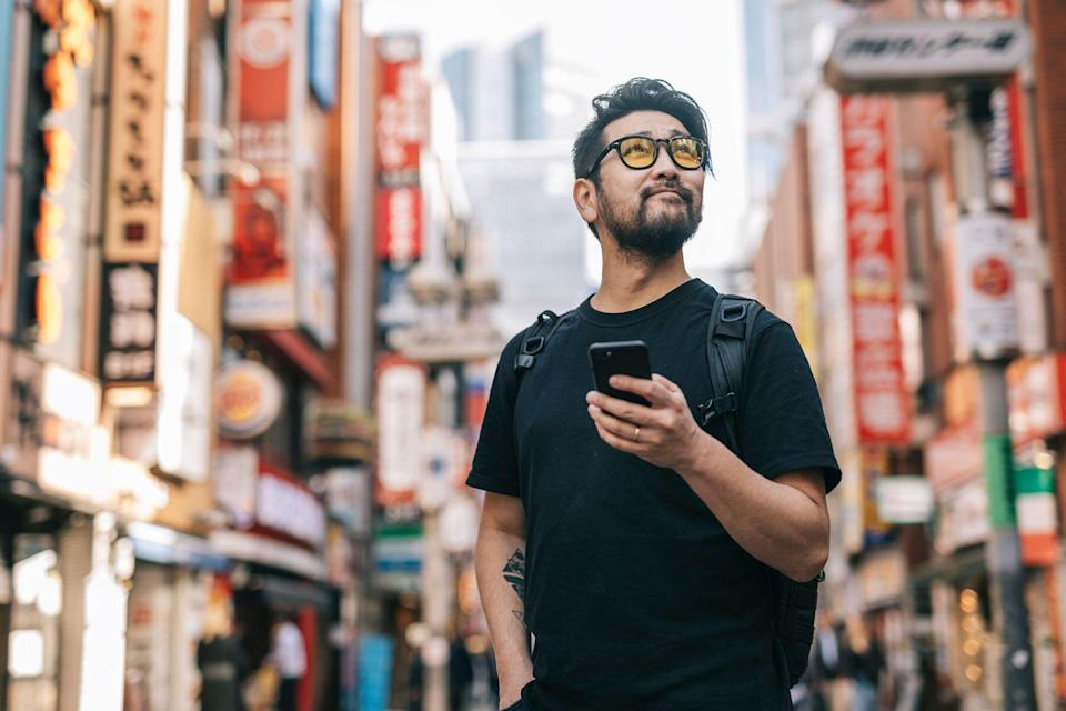 Asian man traveling using cell phone