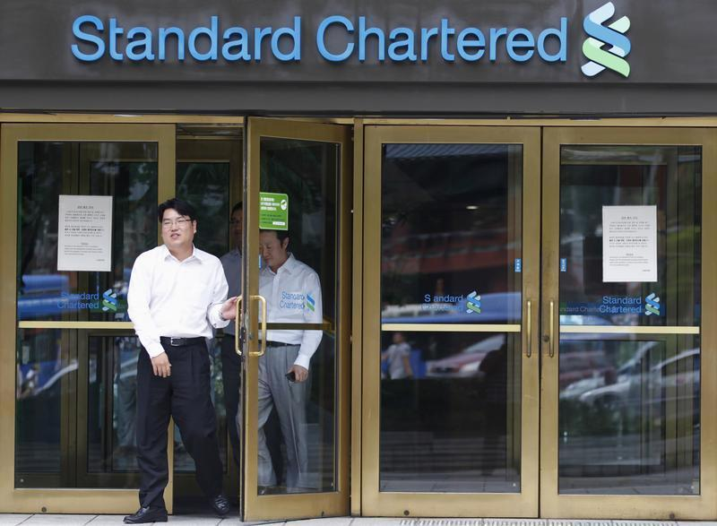 Employees of Standard Chartered leave a branch of the bank in central Seoul