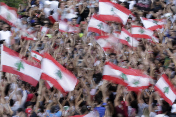 In this photo taken with slow shutter speed, shows anti-government protesters wave Lebanese national flags as shout slogans against the Lebanese government during a protest in Beirut, Lebanon, Saturday, Oct. 19, 2019. The blaze of protests was unleashed a day earlier when the government announced a slate of new proposed taxes, including a $6 monthly fee for using Whatsapp voice calls. The measures set a spark to long-smoldering anger against top leaders from the president and prime minister to the numerous factional figures many blame for decades of corruption and mismanagement. (AP Photo/Hassan Ammar)