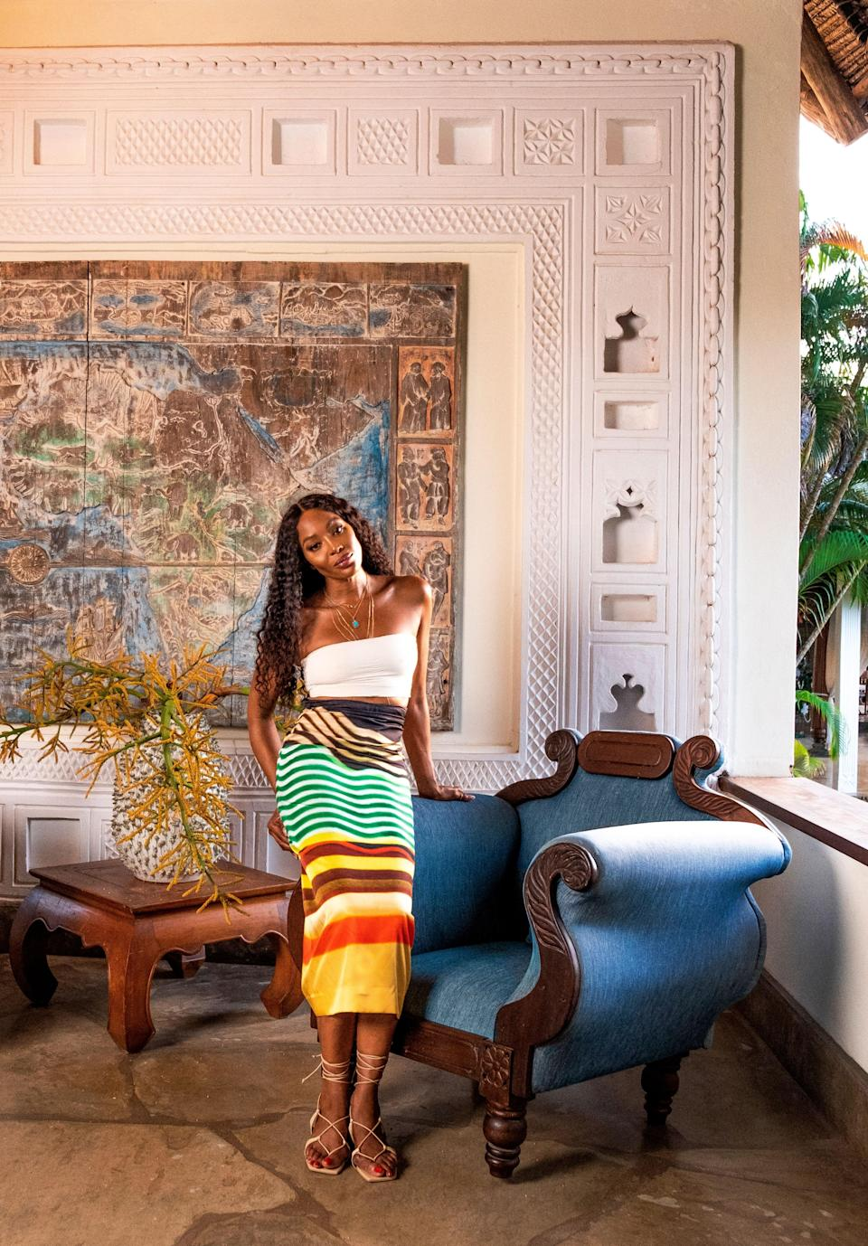 Naomi Campbell, wearing a Jade Swim bandeau top, Dries van Noten skirt, and Cult Gaia sandals, in the entrance area of her Kenyan getaway. On wall, a Bas-relief of Africa by local artist Armando Tanzini. Fashion styling by Carlos Nazario.