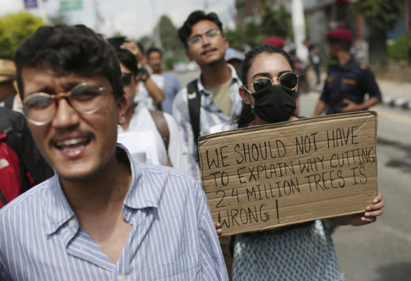 Nepalese activists shout slogans during a protest outside Civil Aviation Authority of Nepal, in Kathmandu, Monday, Aug. 19, 2019. A small group of protesters demonstrated in Nepal's capital against plans to cut down millions of trees for an international airport in the southern part of the country. (AP Photo/Niranjan Shrestha)