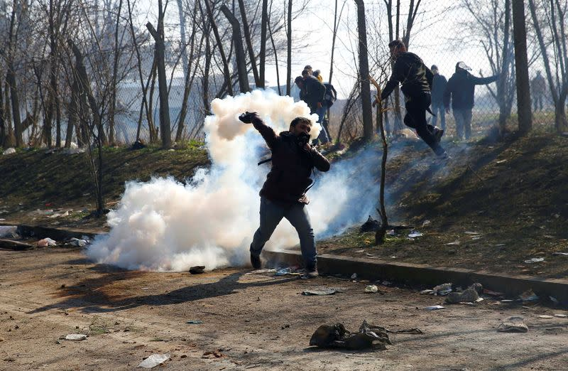 A migrant throws a tear gas canister back during clashes with Greek police, at the Turkey's Pazarkule border crossing with Greece's Kastanies, in Edirne