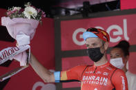 Italy's Damiano Caruso celebrates on podium his second place after completing the final stage to win the Giro d'Italia cycling race, in Milan, Italy, Sunday, May 30, 2021. (AP Photo/Luca Bruno)