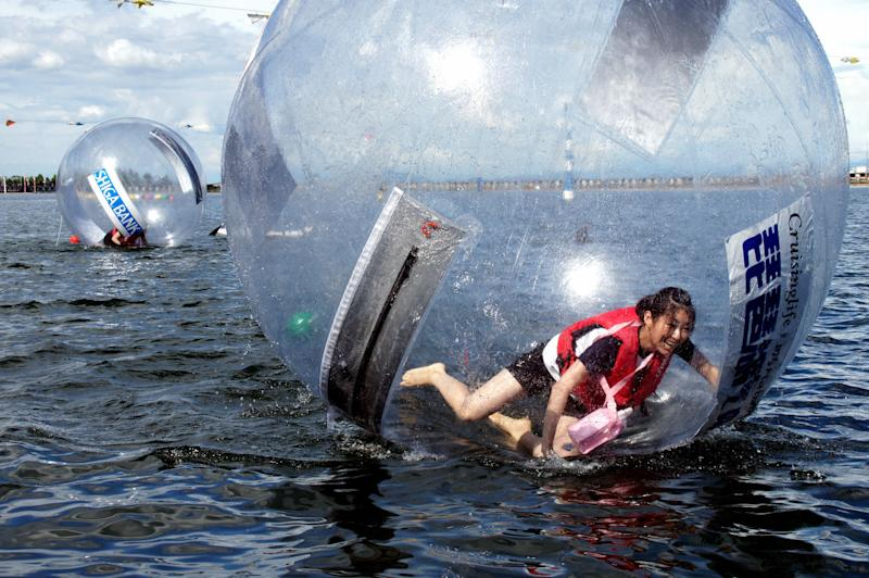 """In this Aug. 9, 2010 photo, a contestant of a """"walking on the water race"""" tries to walk inside a transparent ball in the water in Lake Biwa in Otsu, Shiga Prefecture, western Japan. Two nuclear reactors have passed safety checks and gotten the Japanese government's approval on June 16, 2012 to resume generating power. But communities around the Ohi plant in western Japan feel they aren't ready. If the reactors plunged into a Fukushima-like meltdown, the only route to escape or send help would be a road closed by snow in winter or clogged by beachgoers in summer. Radiation leaks could contaminate the lake that provides freshwater to more than 14 million people. There's no contingency plan. (AP Photo/Kyodo News) JAPAN OUT, MANDATORY CREDIT, NO LICENSING IN CHINA, HONG KONG, JAPAN, SOUTH KOREA AND FRANCE"""