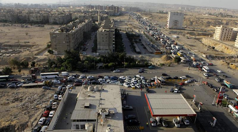 General view showing a traffic jam surround a gasoline station as drivers wait in long queues in Cairo, Egypt, Tuesday, June 25, 2013. Fuel shortages have caused long lines for months, but Egypt's Supply Minister Bassem Ouda told a news conference that the latest fuel shortage will end in a matter of days. Authorities blame the shortage on a technical problem at a major petrol depot on the outskirts of Cairo. (AP Photo/Amr Nabil)