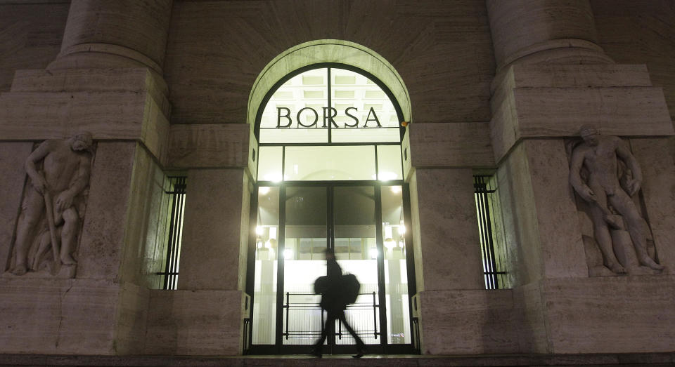 FILE - In this November 21, 2011 file photo, a man walks past the stock exchange building in Milan, Italy. Italy's market watchdog on Monday, July 23, 2012 imposed a week-long ban on the short-selling of financial stocks as the Milan index plunged amid fears that if Spain needs a bailout, Italy could be next. The main stock index, the FTSE-MIB, closed 2.8 percent lower after being down by more than 5 percent in the morning. (AP Photo/Luca Bruno, file)