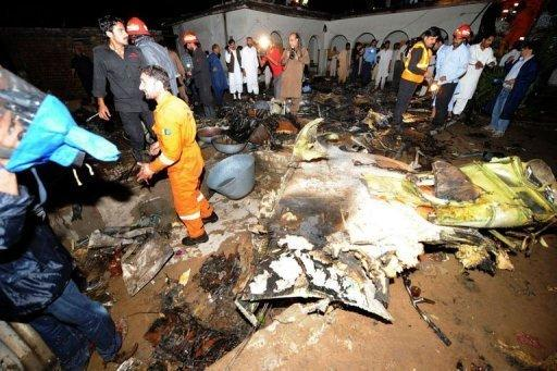 Pakistani rescue workers and local residents search the site of a plane crash in Rawalpindi. The Bhoja Air flight from Karachi burst into flames after coming down in fields near a village on the outskirts of the Pakistani capital as it tried to land in rain and hail at the city's international airport