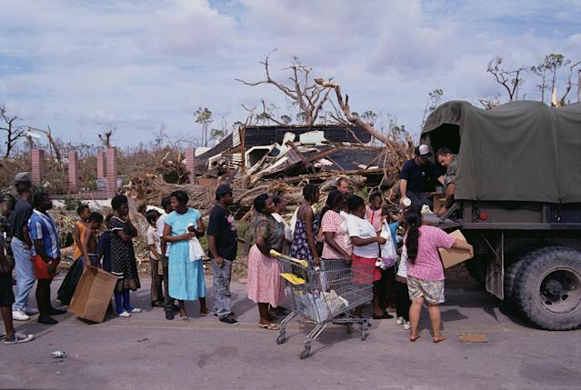 <p>Army personnel pass out supplies from the back of a truck to victims of Hurricane Andrew. (Steve Starr/CORBIS/Corbis via Getty Images) </p>