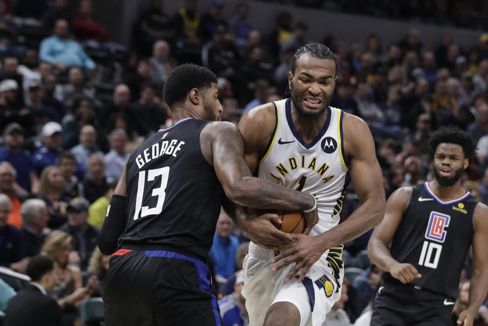 Indiana Pacers' T.J. Warren (1) is defended by Los Angeles Clippers' Paul George (13) during the second half of an NBA basketball game, Monday, Dec. 9, 2019, in Indianapolis. The Clippers won 110-99. (AP Photo/Darron Cummings)