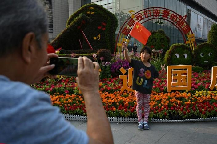 Beijing was decked in red Chinese flags, flower displays, lanterns and political slogans ahead of the tightly-choreographed festivities (AFP Photo/HECTOR RETAMAL)