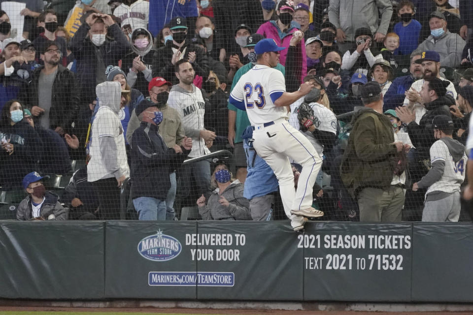 Seattle Mariners first baseman Ty France (23) stands on the wall after a fan on the other side of the safety net caught a pop-up foul hit by Los Angeles Angels' Juan Lagares during the sixth inning of a baseball game, Sunday, Oct. 3, 2021, in Seattle. (AP Photo/Ted S. Warren)