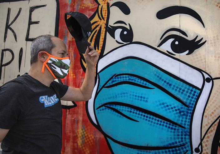 """Neal Brandenburg walks by a mural painted by artist Sara Sandoval on Traction Avenue near 3rd Street in Los Angeles. <span class=""""copyright"""">(Mel Melcon / Los Angeles Times)</span>"""