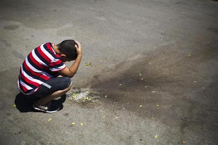 Israeli boy looks at shrapnel at parking lot in the Israeli southern city of Sderot after a rocket fired by Palestinian from Gaza Strip landed in town