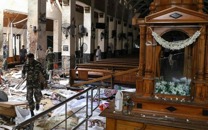 Sri Lankan security personnel walk past dead bodies covered with blankets amid blast debris at St. Anthony's Shrine following an explosion in the church in Kochchikade in Colombo - AFP or licensors