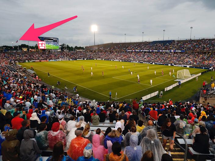 A red arrow points to an American flag flying at the far end of Rentschler Field in Connecticut.