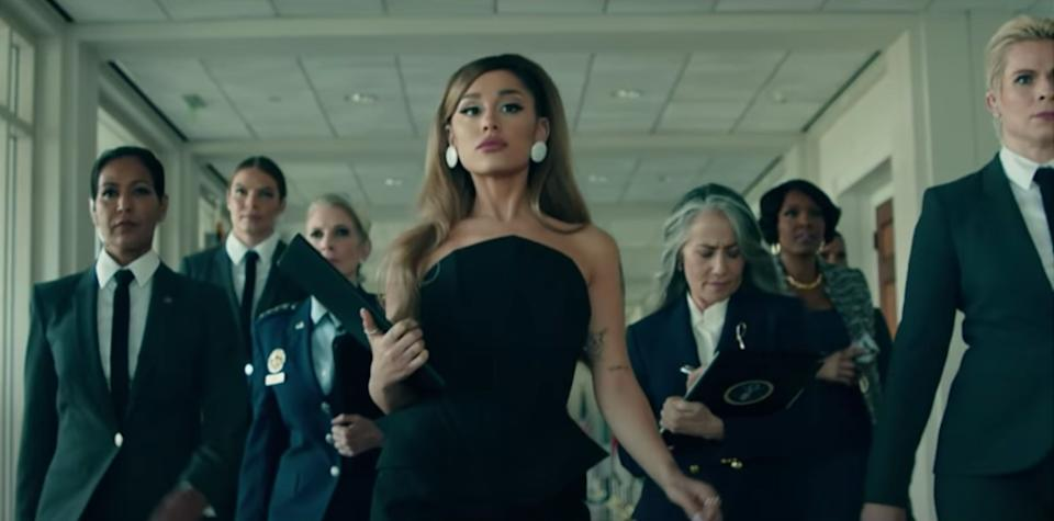 Ariana is flanked by a group of female aides (Photo: YouTube)