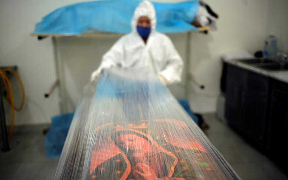 An employee of a Rio funeral home wraps a casket containing the body of a person that died from Covid-19 - Reuters